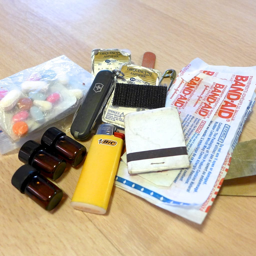 FIRST AID KIT: cuben fiber tape, ibuprofen, benadryl, vicodin, match book, mini-bic lighter, emery board, extra pair of contacts, tough strips band-aids, essential oils, safety pin, knife